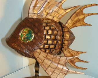 Wooden fish has a brick design on body. Has greenish gold crystal eyes with gold outline.