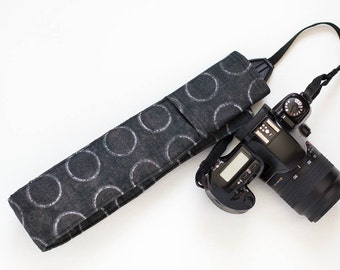 DSLR camera strap cover with lens cap pocket.  black with white circles.