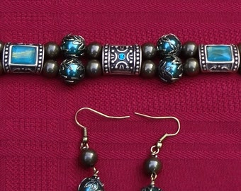 Antique Brass Finish Double Strand Bracelet with Brass Spacers and Capped Teal Beads and Crystal Inset.
