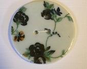 White porcelain button with tiny dark flower chintz design