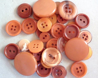 Lot of more than two dozen mixed size/style orange/rust plastic buttons