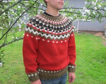 Men's handknit rust sweater with black, cream and olive accents.
