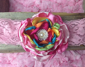 Satin petal flower with pearl center. Available in any color combo