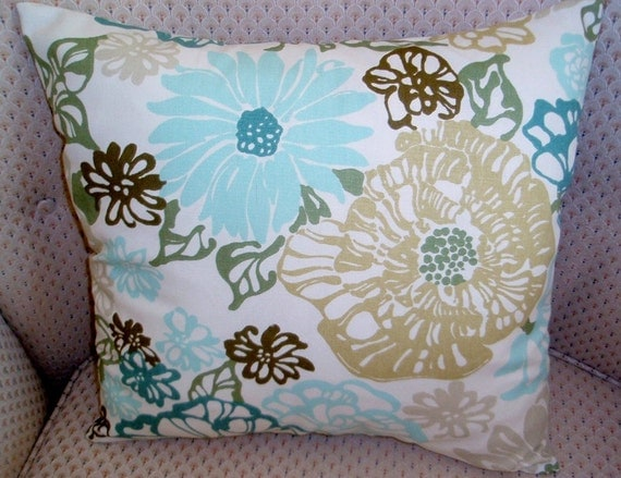 Pillow cover with muted flowers and leaves on an off white background