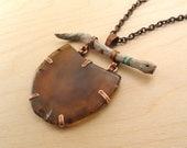 Brown Half Oval Agate with a Copper Setting Hanging from a Painted Stick