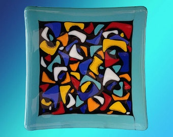 "Plate, 8"" square fused glass decorative with solid blue border and colorful abstract design on black in center"