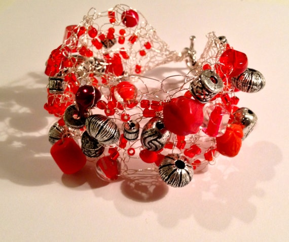 Handmade silver beaded wire crochet cuff bracelet with various types, sizes and shapes of metal and red beads