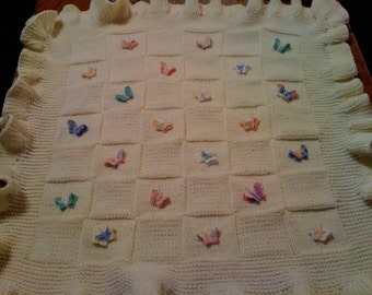 Knitted baby blanket with crochet butterflies