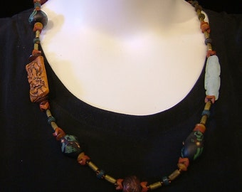 Ethnic look, African trade brass tubes, Bohemian snake beads, carved serpentine and polymer beads.  31 inches, magnetic clasp