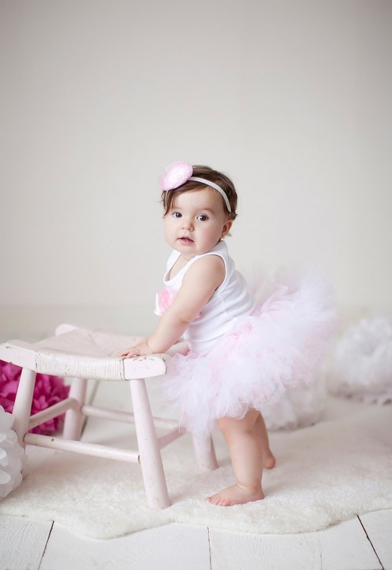 This adorable ballet dress features a pinch-front camisole-style bodice, crisscross straps and a charming two-tier tutu-style skirt with a trendy surplice waistband. Matte nylon/spandex has plenty of stretch to allow for maximum ease of movement, and a full front liner helps keep little dancers.