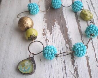Paisley Tapestry bracelet- hand formed beaded bead chain. turquoise. chartruese. artisian ceramic clasp. enamel flower. Jettabugjewelry
