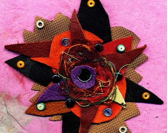 Leather Explosion..a dramatic brooch made from leather, suede and threads with mirror