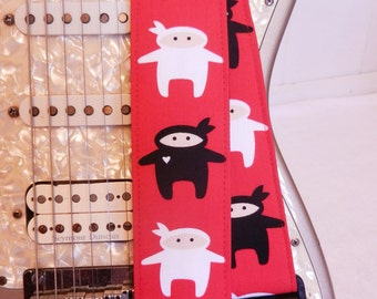 Black and white ninjas on red guitar strap