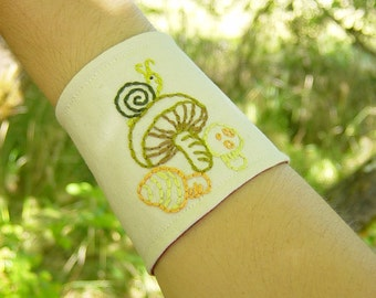 Hand embroidered large fabric cuff bracelet made from vintage reclaimed materials, snail and mushrooms