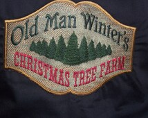 397 Black chef's style bib apron with Old Man  Winter's Tree Farm embroidery.