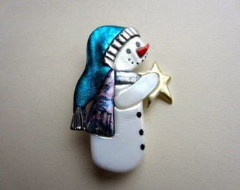 Snowman with teal stocking cap and patterned scarf holding a star pin brooch
