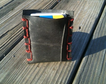 Upcycled rubber tire business card holder with red hemp stitching.