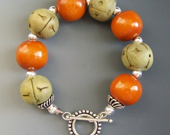 Large orange wooden beads, green-taupe carved beads, sterling beads and toggle