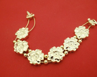 "Vintage New Old Stock NOS 7.5""  gold tone slide bracelet with gold tone charms, New Old Stock in unworn condition"