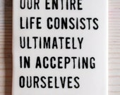 porcelain tag screenprinted text our entire life consists ultimately in accepting ourselves as we are. -jean anouilh