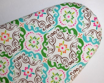 Standard Ironing Board Cover in pinks, blues, and greens on an off white background.