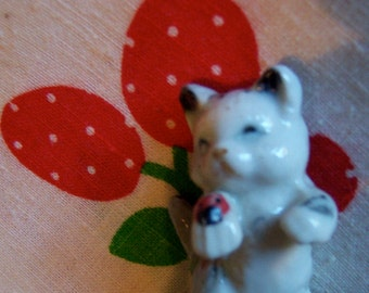 miniature gray tabby with ladybug figurine