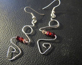 Wire wrapped abstract earrings in sterling silver with red and pink crystals