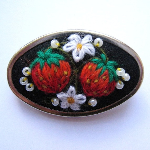 Hand art embroidery brooch with mellow strawberries in silver colored frame.