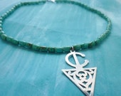 Moroccan turquoise gemstone bead and sterling silver Berber symbol charm necklace