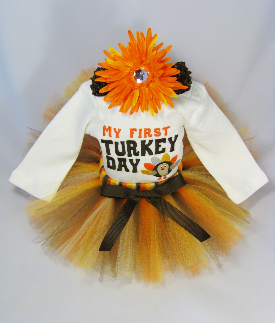 Baby Girl size 12 months, My First Gobble, Thanksgiving Outfit. Long sleeve onesie, features gold cursive and the tutu has brown glitter tulle on top, purple, then mustard, then gold tulle layers. All.
