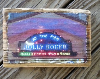 Color photograph featuring the Jolly Roger sign at the pier in Ocean City Maryland transferred onto reclaimed boardwalk wood