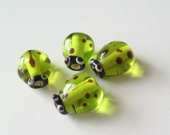 Glass ladybug beads light green 4 pcs.