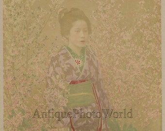 Young woman geisha in sakura garden antique hand tinted photo Japan