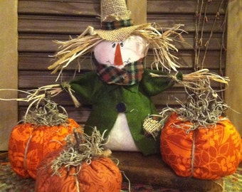 Primitive Country Fall Scarecrow in pumpkin patch with three pumpkins