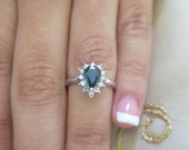 14K White gold Pear shape sapphire and round diamond ring.