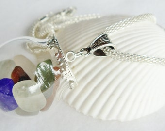 Nautical glass orb necklace encloses  smooth sea glass with silver accents