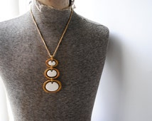 Modernist vintage 70s gold tone metal necklace with a vertical, cascade oval shape, three tier pendant with   lucite. Made by Trifari crown.
