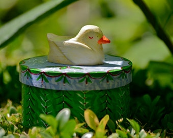 Round wooden trinket box with a sleeping duck on top