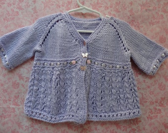 KNITTTED: Baby, toddlers sweater, hand knitted in a delicate, lacey pattern, with ribbon and pink rosettes