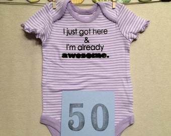 DISCOUNTED -- Good but Not Perfect -- #50, see photos -- I just got here & I'm already awesome - purple striped bodysuit, size 0-3 months.