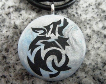 Wolf hand carved on a polymer clay blue/grey pearl color background. Pendant comes with a FREE Necklace