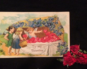Valentine Postcard - Girl and Boy - Cupid selling Hearts - Violets