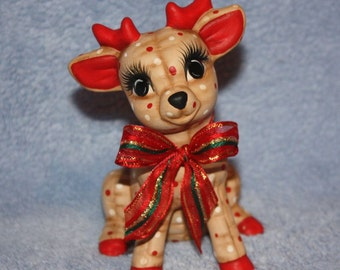 Handpainted Ceramic Christmas Reindeer Baby Sitting painted with a holly berry print to look stuffed