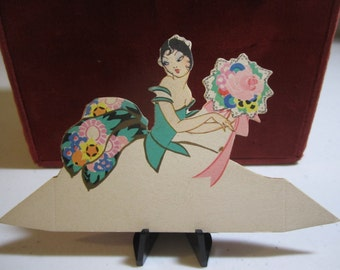 Die Cut  gold gilded unused 1920's Buzza place card pretty lady in elaborate gown holding a large bouquet of flowers