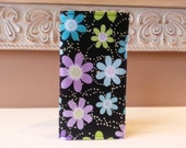 Checkbook cover, reciept holder, coupon carrier in black background and colorful flowers and purple lining