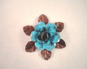 Medium Size Decorative Metal Hand Cut and Hand Painted Rustic Blue Color Rose Mounted on a Bed of Leaves.
