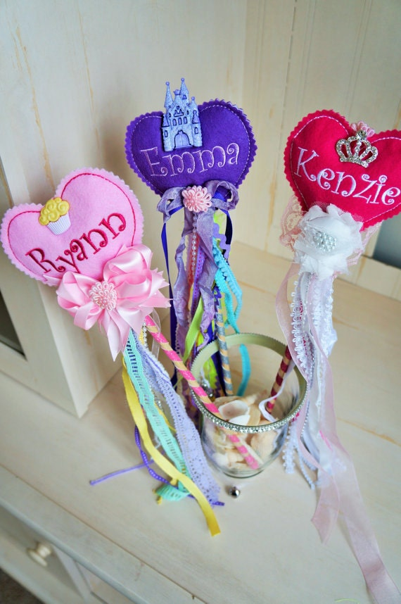 Fairy Wand. Two sided felt stuffed heart with a child's name, embellishments, ribbons, bows, bells and more on a glittery wooden stick
