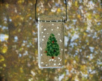 Fused glass ornament sun catcher with snow flakes and a decorated Christmas tree on clear glass with wire and bead accents.