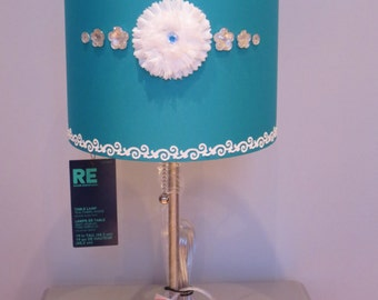 Girly Glam Lamp with teal lamp shade, white floral embellishment w/teal center stone, crystal-like embellishments & white sparkle border.