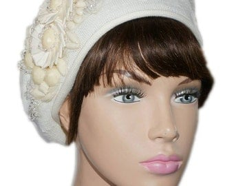 Ivory beret adorned with elegant appliques made of pearls, stones and ribbons.